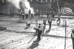 Construction workers laying foundation of building.