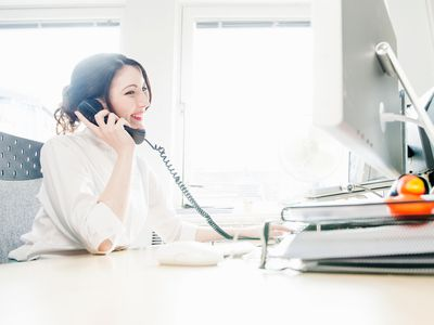woman on telephone in front of computer in office
