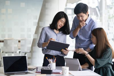 Two women and a man consult about data in an office.
