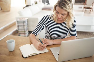 High angle shot of an attractive young woman writing in her journal while surfing the net