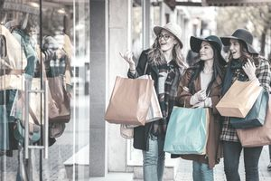 three girls wearing large hats on a shopping spree