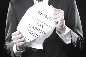 A man in a suit holding a tax liability notice