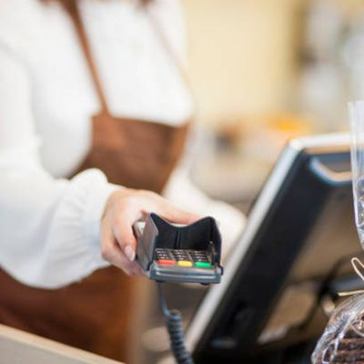 Female cashier using a CPU and waiting on a customer to pay