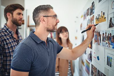 Man working on graph with colleagues
