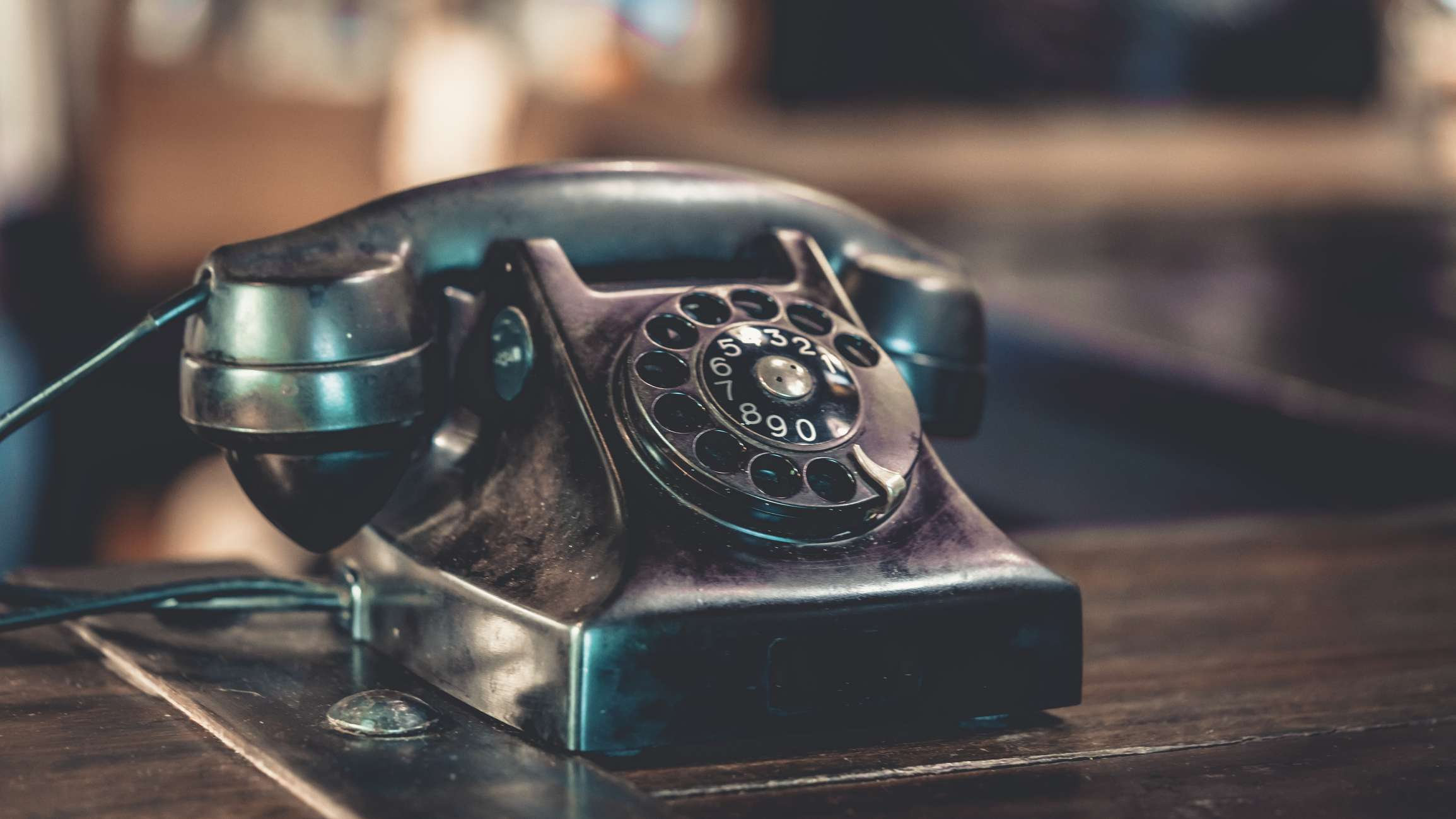 Traditional landline phone which has become a thing of the past sitting on a desk.