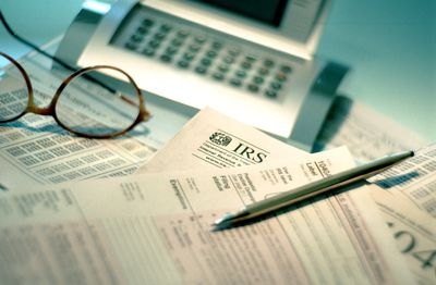 Closeup of a pen and eyeglasses sitting atop a tax return