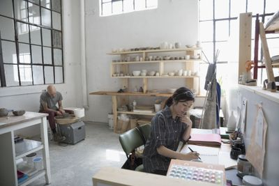 Artists sketching and using pottery wheel in art studio