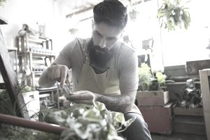Terrarium shop owner with beard pruning plant