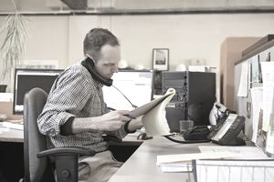 Businessman checks cold call script while cold calling potential customers