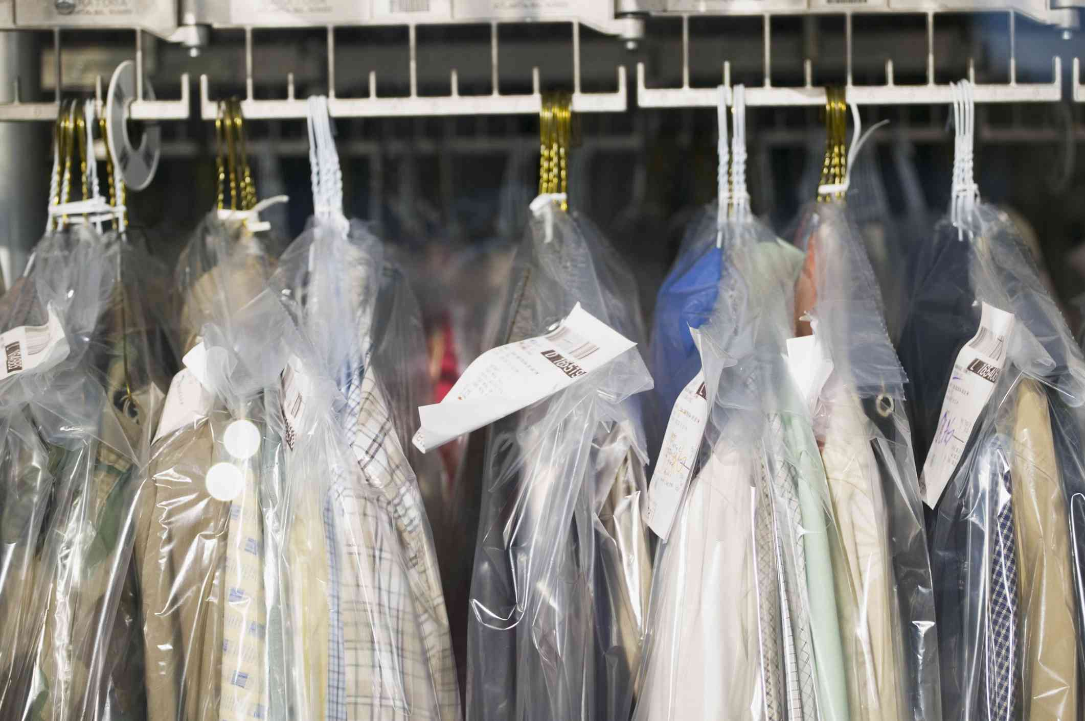 Shirts wrapped in plastic hanging on a rack