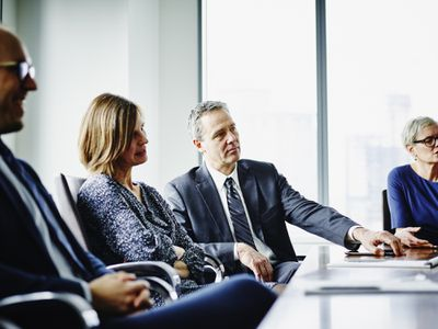 Business executives around a conference table meeting to discuss capital investment projects.