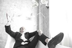 Man sitting on chair throwing money in the air