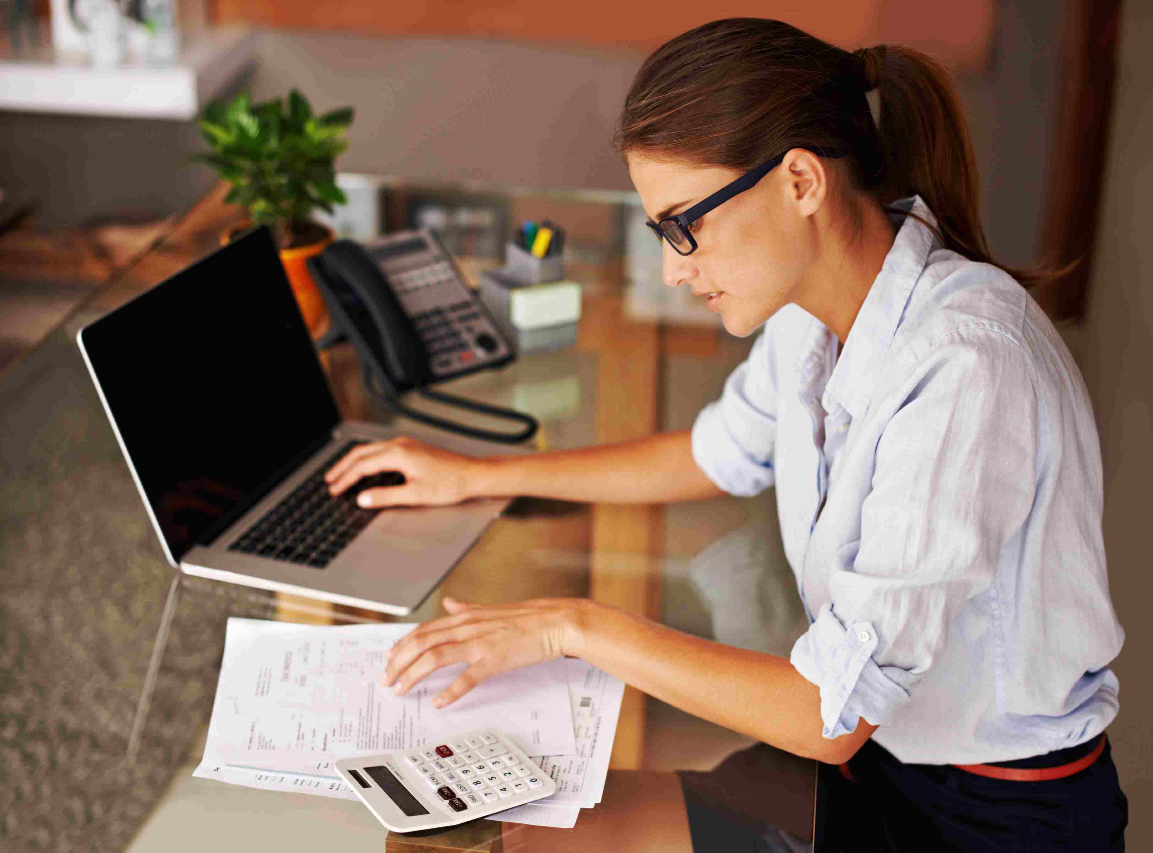 Woman entering income tax receipts on her laptop