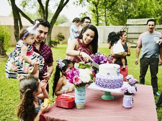 Mother cutting cake for daughter during first birthday party with family in backyard