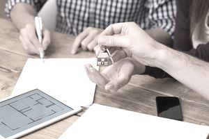 Close up hands receiving house keys with online floorplan on a tablet.