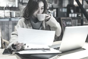 Freelancer looking at tax paperwork in coffee shop