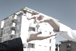 person handing key to another in front of building