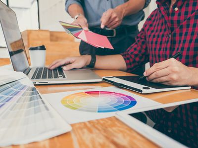 Business Colleagues Discussing Over Color Swatch On Desk In Office