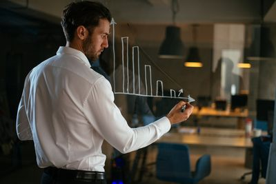 man looking at chart of business trends of the 21st century