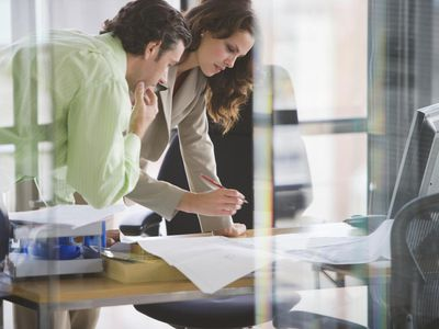 Businesswoman and man working on marketing plan in office