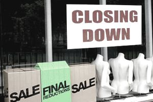 """""""Closing Down"""" sign hung in a store window, hanging over mannequins and boxes"""