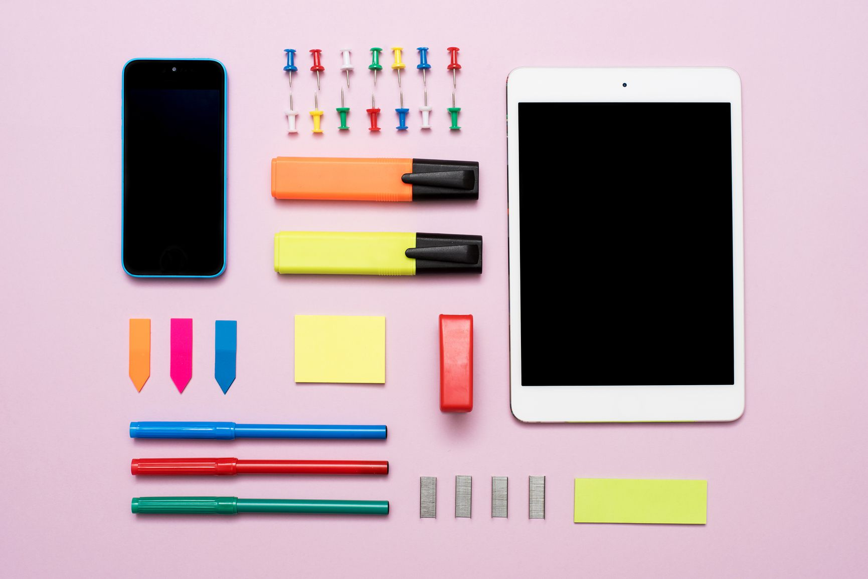 A smart phone, tablet, flash drives, and pens against a light purple background