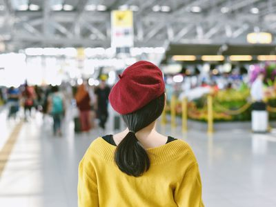 Woman wearing beret walking in to trade show exhibition hall.