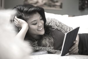 Young woman laying on bed reading eBook on digital tablet