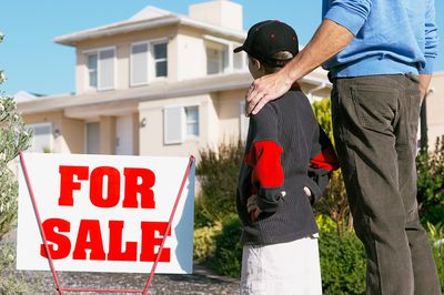 Father and son looking at house for sale