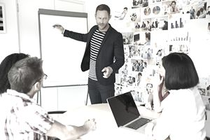 A marketing professional standing in front of a whiteboard presenting a project to a group seated at a table.