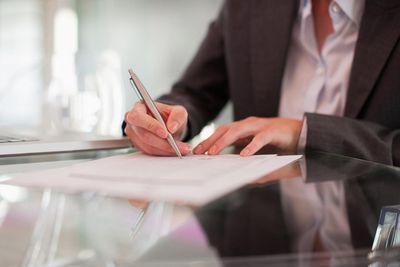 A businesswoman signing a contract while sitting at a desk