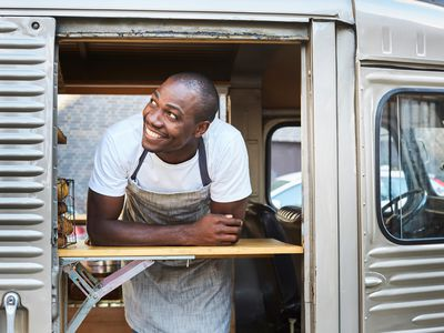 Smiling mid adult male owner looking away while standing in food truck