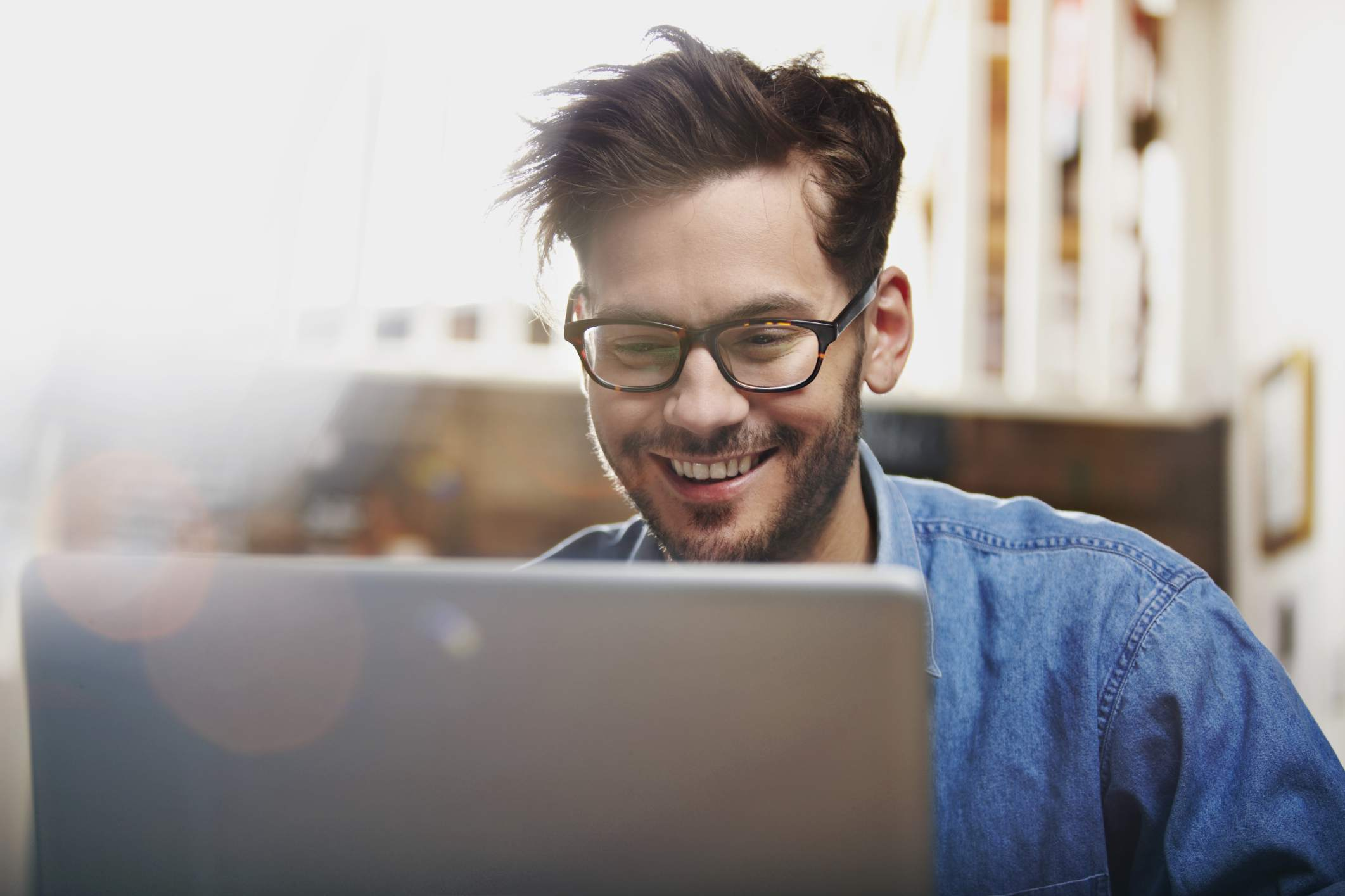 a young businessman in front of a laptop smiling