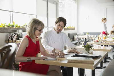 Bistro owner and chef planning menu at table
