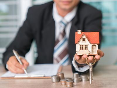 Man holding model of house and keys with piles of change on the table assuming a mortgage.