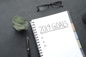 Notepad with a goal list, pen, glasses, and plant