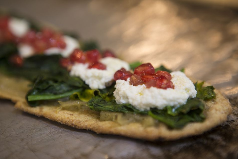 Spanish tapas with spinach, soft cheese and pomegranate seeds on flatbread