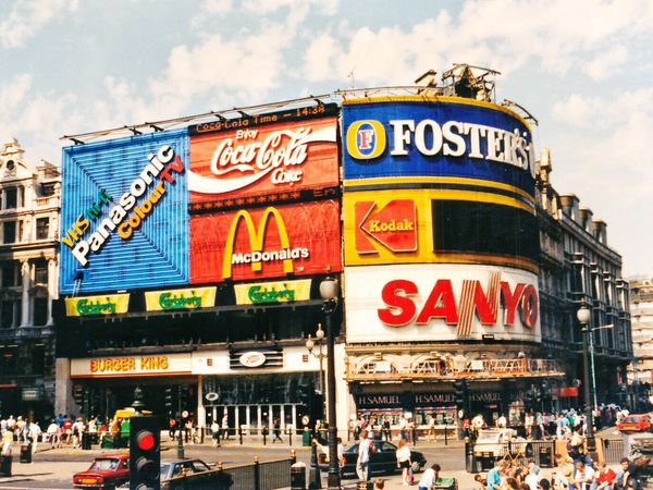 Vivid company logos on billboards mounted to the side of a building on a busy street corner..