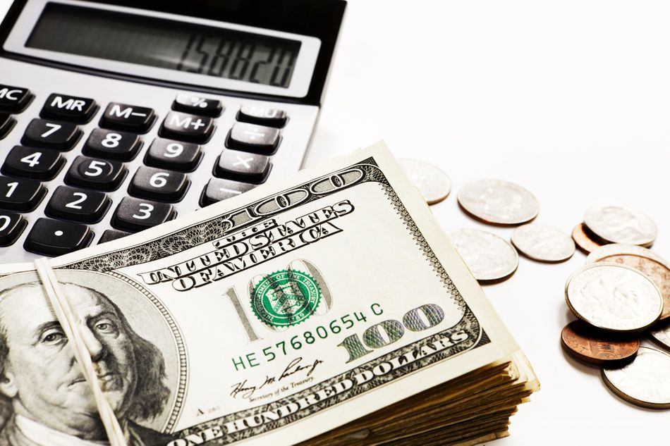 Bundles of US dollars and coins with calculator