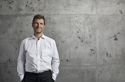 Man in white dress shirt standing in front of a concrete wall