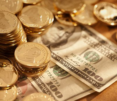 Gold coins with hundred dollar bills