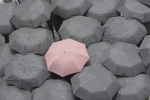 One red umbrella at center of multiple black umbrellas