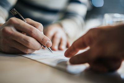Close up of unrecognizable man signing a contract while second man points at place to sign