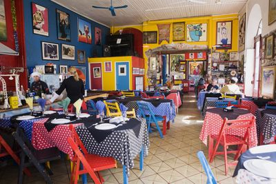 A restaurant decorated with bright multi-colored walls, tablecloths, chairs and artwork.