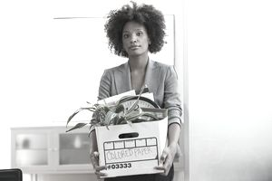 Woman Leaving Office After Layoff With Box of Her Belongings
