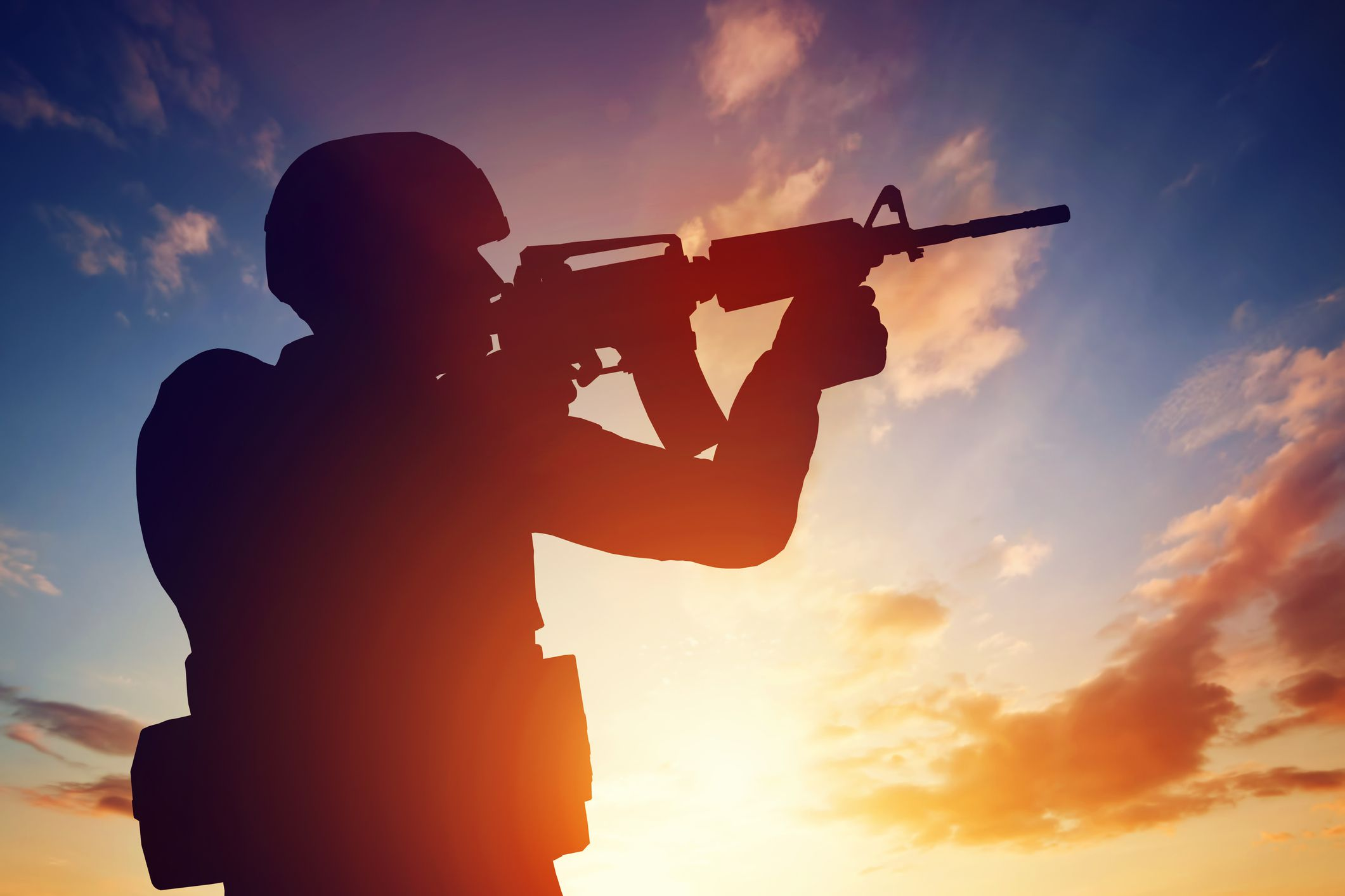 Soldier firing rifle at sunset