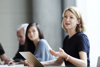 Woman with computer open in front of her explaining something at a conference room table