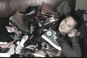Tony Hsieh laying under a pile of shoes