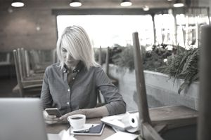 a businesswoman using her phone at a table in front of a laptop and ten key