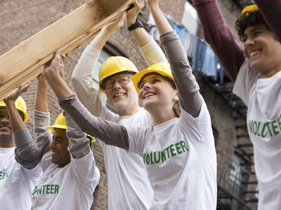 Group of volunteers helping to build a house.